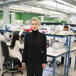 Elizabeth Holmes, a young white woman with her blond hair in a ponytail, stands in a black turtleneck in a medical lab