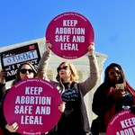 women of all races and ages hold pink Keep Abortion Safe and Legal signs