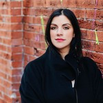 Erin Khar, a white woman with black hair and brown eyes, stands against a brick wall. She wears a black coat and has a soft smile.