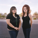 two young women standing side-by-side in an open parking lot