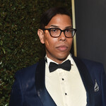 Steven Canals, a Latinx man with short, black hair and glasses, wears a blue tuxedo at a formal event