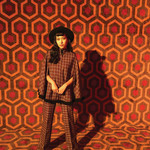 Felicia Wade wearing a 1970s plaid pantsuit in front of a vintage geometric background