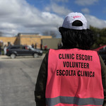 "photo of the back of a person wearing a bright pink abortion clinic escort vest with the words ""Clinic Escort Volunteer Escolta Clinica"""