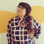 photo of Gloria Lucas in a patterned shirt wearing glasses and looking off to the side