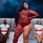 photo of Lizzo posing on stage wearing an embellished red body suit with two curvy back-up dancers standing behind her