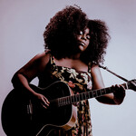 Yola, a dark-skinned Black woman with a short, curly afro, poses against a pale purple and blue background, playing her guitar