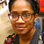 Photo of author Bethany C. Morrow wearing glasses and patterned headband sitting in a bookstore