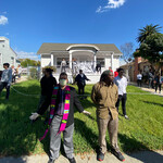 Community members, some of whom are white and some of whom are Black and Latinx,  stand together on the lawn of a house in Los Angeles