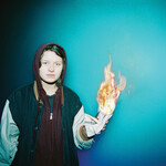 Marie Ulven Ringheim wearing a hoodie holding a piece of paper that is on fire.
