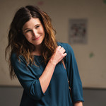 Kathryn Hahn plays Eve Fletcher, a middle-age white woman with shoulder-length brown hair who's standing awkwardly in a teal sweater with her hand on her purse