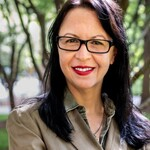 Author Jennifer Keishin Armstrong, who wears a brown linen blazer, has dark hair, and wears red lipstick and glasses.