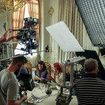 Jessie Mei Li as Alina Starkov (left)and Daisy Head as Genya Safin on the set of Shadow and Bone. They are setting at an ornate table opening a letter. Four crew members are holding cameras and boom mics while filming the scene.