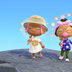 A screenshot from Animal Crossing. Two players, both with brown skin, one with pink hair, one with a bun and a pacifier, sit on a rock by the ocean.