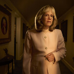 A frowning, frumpy Linda Tripp stands in a shadowed hallway