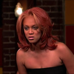 Tyra Banks has red hair with blond highlights. She looks seriously at someone who isn't in the shot.