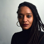 Tatyana Fazlalizadeh, a Black woman, wears gold hoops and dark red lipstick and looks at the camera. Her hair is in long braids and she wears a black sweater.
