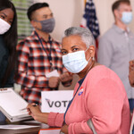 An older woman with brown skin and white hair sits and wears a face mask while voting.