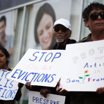 three residents of a San Francisco apartment hold Stop Evictions sign during a protest