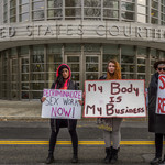 three protestors hold sex work is work signs in front of Brooklyn's gray United States Courthouse