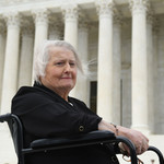 Aimee Stephens, an elderly trans white woman in a wheelchair, sits in front of the steps of the Supreme Court