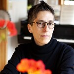 Alison Bechdel, a thin, white person with short brown hair and glasses, is wearing a black turtleneck and looking somberly at the camera