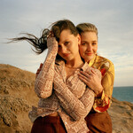 Aly & AJ, two young white women brown hair, pose together on the beach with their arms entwined