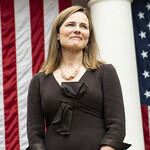 Amy Coney Barrett, a white woman with short, brown hair, stands in front of an American flag wearing a black dress
