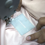 In New Dehli, a worker sews an Everlane label on a leather jacket.