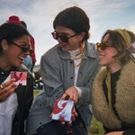 Three young women in sunglasses and coats (one Brown woman with a brown braid and two white-passing women with their brown hair pulled off their faces) hold boxes of tampons and pads in August's advertisement.