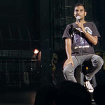 Aziz Ansari wears a Metallica t-shirt and sits on a stool on stage with a microphone in hand