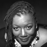 black and white photo of a Black woman with chin-length locs who's wearing a Black shirt and silver and black necklace