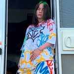 Billie Eilish, a white young woman, has black-dyed hair and is very pale. She leans out of a trailer and wears an oversized, pastel-colored outfit.