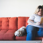 a white plus-size woman reading on couch with a dog