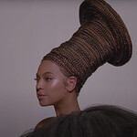 A screenshot of Beyoncé in Black is King. Beyoncé looks regal, her expression soft and her face looking to the side. There's a glow on the entire image.