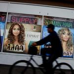 A bicyclist pedals past a beauty supplies shop.