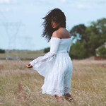 A Black woman with long curly hair wears a light blue long sleeved dress and stands in a field.