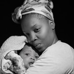 a Black mother in a headwrap holds her newborn baby to her chest