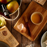 A wooden cutting board and the ingredients for apple pie sitting on a wooden surface