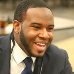 Botham Jean, a Black man with short, Black hair, smiling in a photo