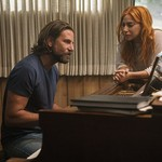 white man with brown hair and white woman with red hair sitting at a piano