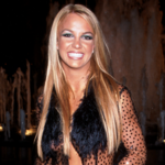 Britney Spears, a white teenager with long, blond hair, smiles brightly at the camera while wearing a black dress