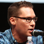Bryan Singer wearing a blue flannel and speaking into a microphone at Comic Con
