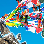 a collage of hikers in colorful gear walking on top of prayer flags toward a mountain
