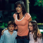 a still of a white woman standing outside looking terrified while flanked by two children