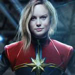 Brie Larson stares at the camera defiantly, her hands on her hips, wearing a red, blue, and gold Captain Marvel suit