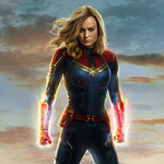 Captain Marvel wears a red and blue suit, gloved fists glowing, and a look of defiance on her face