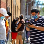 Jeffrey Tellez, a Latinx man wearing a mask and a striped white and navy blue shirt, holds an electronic pad in front of a Latinx man wearing a blue mask and a white hat