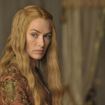 Lena Headey as Cersei Lannister, who has long wavy blonde hair and a medieval style dress, staring soberly offscreen