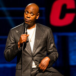 Stand-up comedian Dave Chappelle speaking into a microphone on stage in a black leather jacket