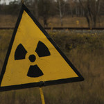 A yellow, triangular radiation warning sign in the Chernobyl Exclusion Zone